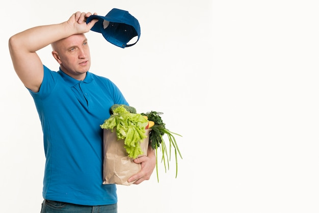 Fatigued delivery man posing with grocery bag Free Photo