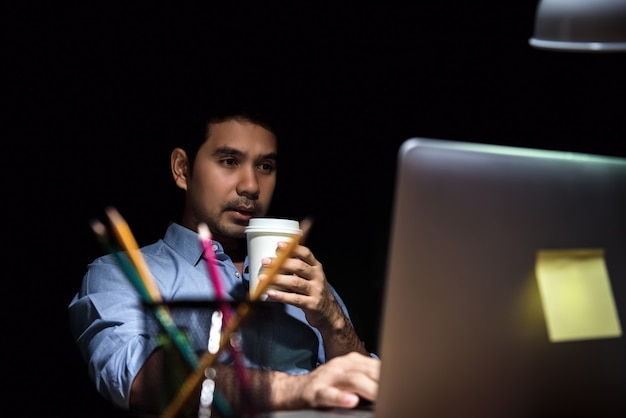 Fatigued office worker working in front of computer at night Premium Photo