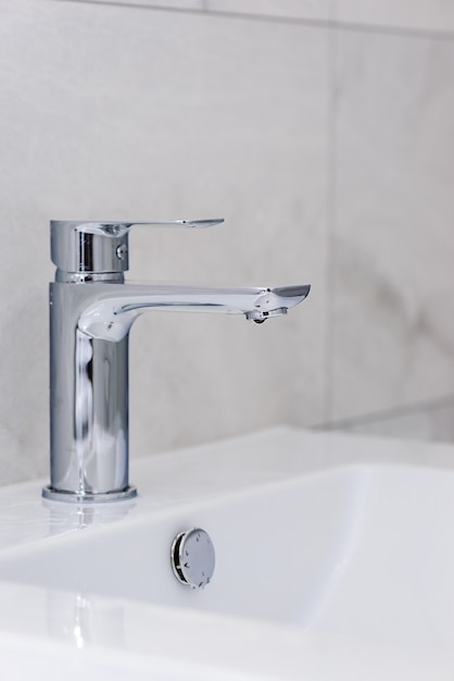 Faucet with a drop of water and a sink on a wall of gray tiles. bathroom interior after renovation. saving water concept. Premium Photo
