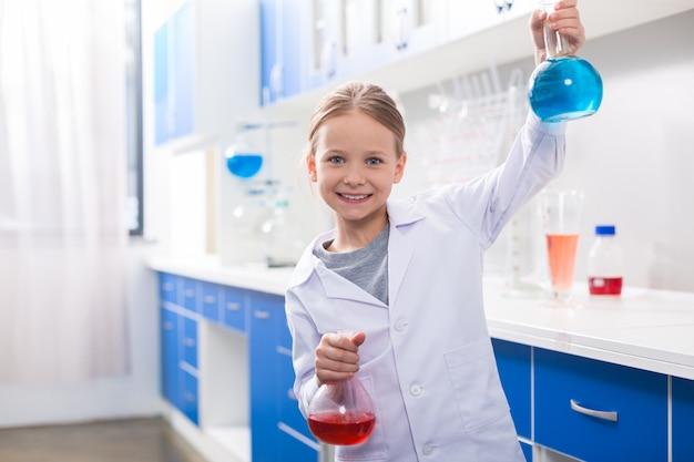 好きな科学。化学実験室にいる間、笑顔でフラスコを持って幸せな幸せな女の子 Premium写真