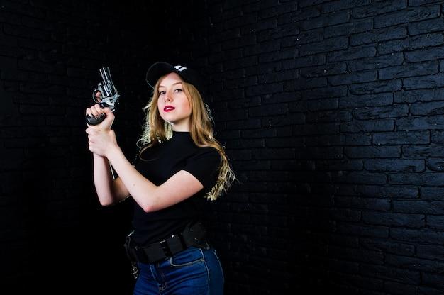 Fbi female agent in cap and with gun against dark brick wall. Premium Photo
