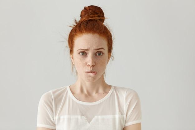 Страшная молодая кавказская женщина с рыжими волосами, одетая в белую блузку, смущенно виновата, кусает нижнюю губу, сожалеет о том, что сделала что-то не так, и делает ужасную ошибку Бесплатные Фотографии