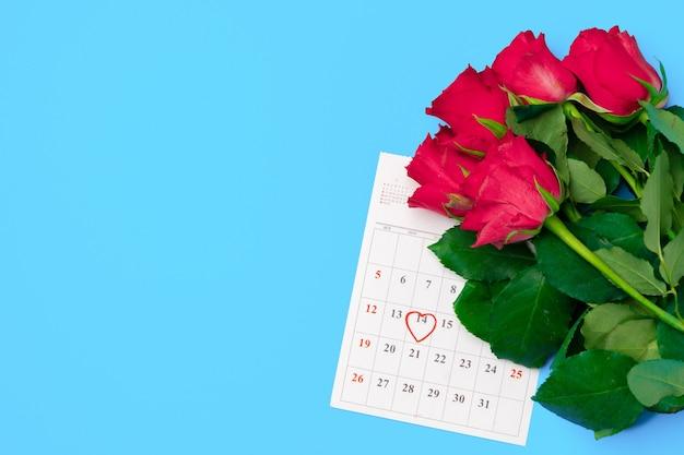 2月のカレンダーと赤いバラの上面図 Premium写真