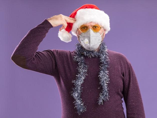 Stufo uomo di mezza età che indossa cappello santa e maschera protettiva con ghirlanda di orpelli intorno al collo con gli occhiali che fa gesto di suicidio isolato sul muro viola Foto Gratuite