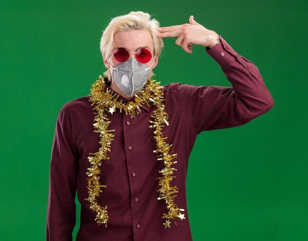Stufo giovane biondo con gli occhiali e maschera protettiva con tinsel ghirlanda intorno al collo guardando la telecamera facendo gesto di suicidio isolato su sfondo verde Foto Gratuite