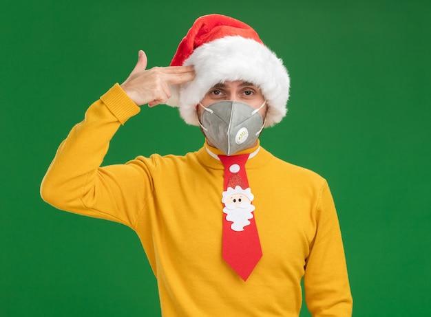 Stufo di giovane uomo caucasico che indossa cappello di natale e cravatta con maschera protettiva facendo gesto di suicidio isolato sulla parete verde Foto Gratuite