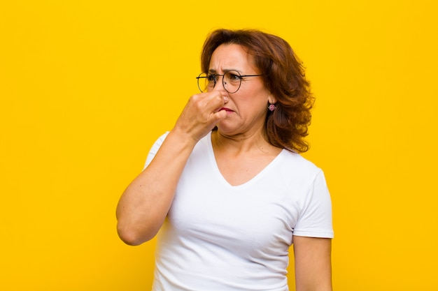 Feeling disgusted, holding nose to avoid smelling a foul and unpleasant stench Premium Photo