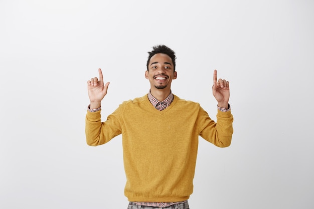 Feeling like winner. portrait of satisfied happy african-american guy in yellow pullover, raising index fingers and pointing upwards, being pleased with positive result, triumphing from good news Free Photo