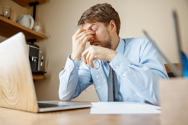 Чувство усталости и тошноты. разочарованный, грустный несчастный больной молодой человек массирует голову, сидя на своем рабочем месте в офисе. Бесплатные Фотографии