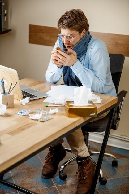아프고 피곤함. 사무실에서 일하는 뜨거운 차 한잔과 함께 남자 무료 사진