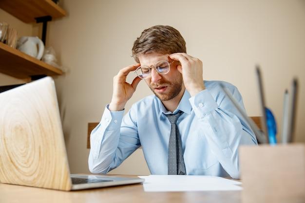Sensazione di malessere e stanchezza. frustrato triste infelice giovane malato che massaggia la testa mentre era seduto al suo posto di lavoro in ufficio. Foto Gratuite
