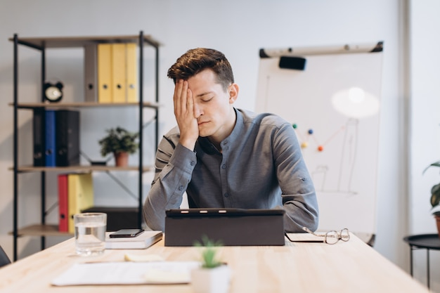 Feeling sick and tired. frustrated young man massaging his nose and keeping eyes closed while sitting at his working place in office Premium Photo