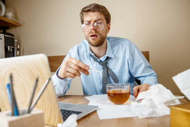 Sensazione di malessere e stanchezza. l'uomo con una tazza di tè caldo che lavora in ufficio, uomo d'affari preso raffreddore, influenza stagionale. influenza pandemica, prevenzione delle malattie, aria condizionata in ufficio causano la malattia Foto Gratuite