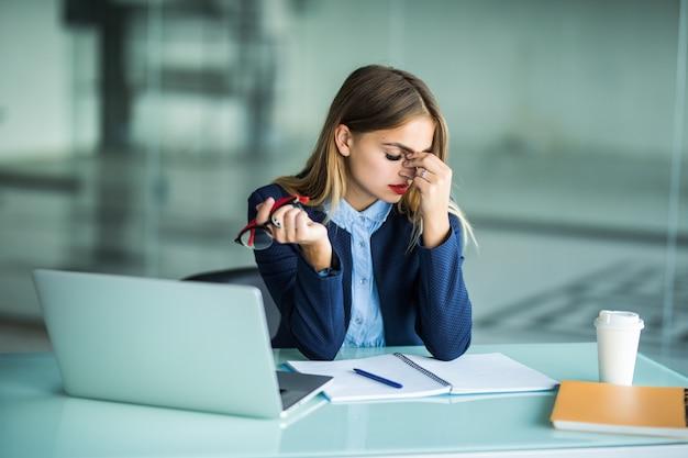 Чувство усталости и стресса. разочарованная молодая женщина с закрытыми глазами массирует нос, сидя на своем рабочем месте в офисе Бесплатные Фотографии
