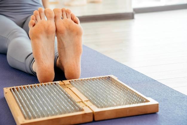 Ноги и деревянная доска с острыми металлическими гвоздями. доска для ног садху. практика релаксации йоги Premium Фотографии