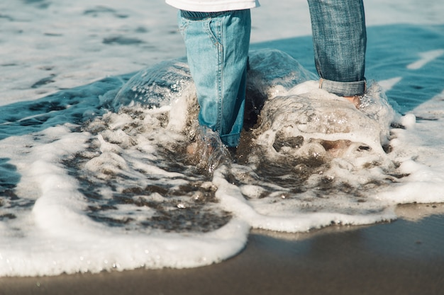 Feet of baby and mother standing in sea Free Photo