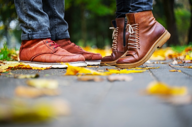 Feet of a couple in love in brown shoes on the path of the autumn park, strewn with fallen leaves. girl stands on toes. kiss concept Premium Photo