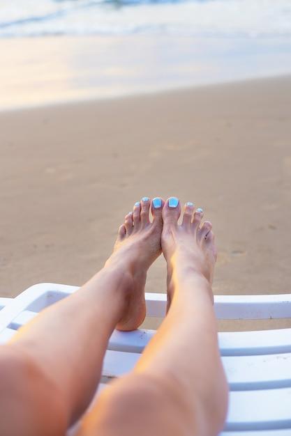 Feet of a girl on a deck chair on the beach Premium Photo