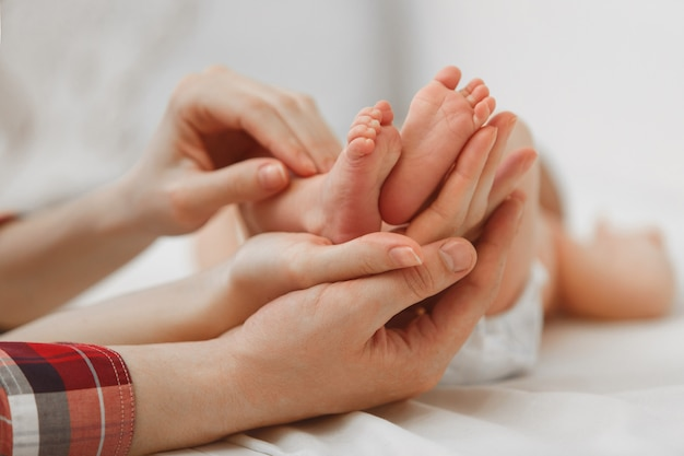 Feet of newborn baby on mother's palm in white background Premium Photo