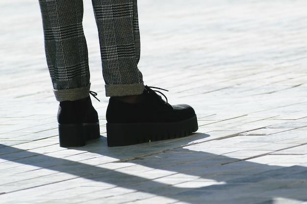 黒いハイシューズと通りに灰色のズボンを持つ女性の足 無料写真