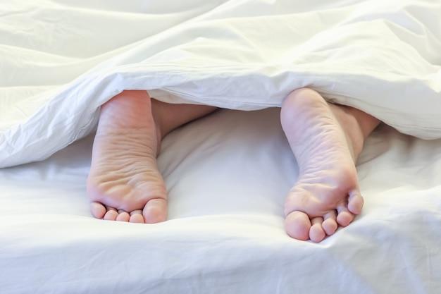 Feet of sleeping woman in white bedroom Premium Photo