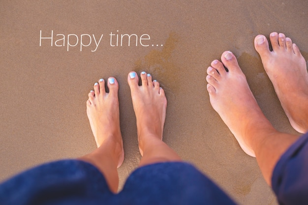Feet of two people on the sand Premium Photo