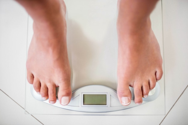 Feet of woman on weighting scale at home Premium Photo