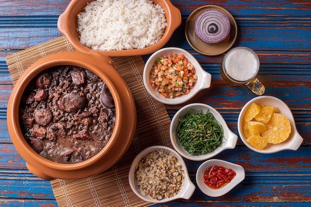 Блюдо фейжоада из черной фасоли, свинины и колбасы Premium Фотографии