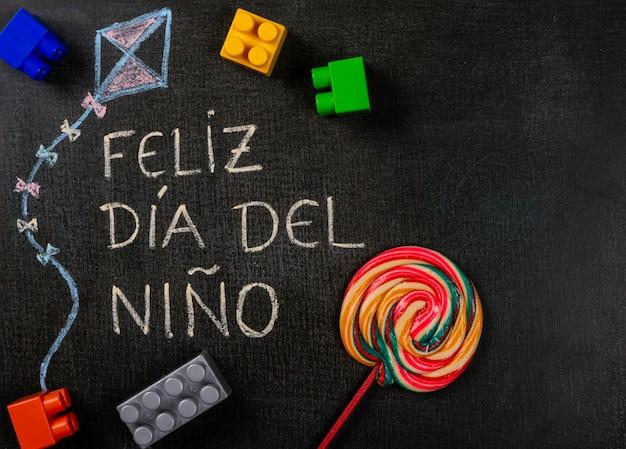 黒板に書かれたfeliz dia delniño(スペイン語)。組み立て部品とロリポップを使用したkのデザイン Premium写真