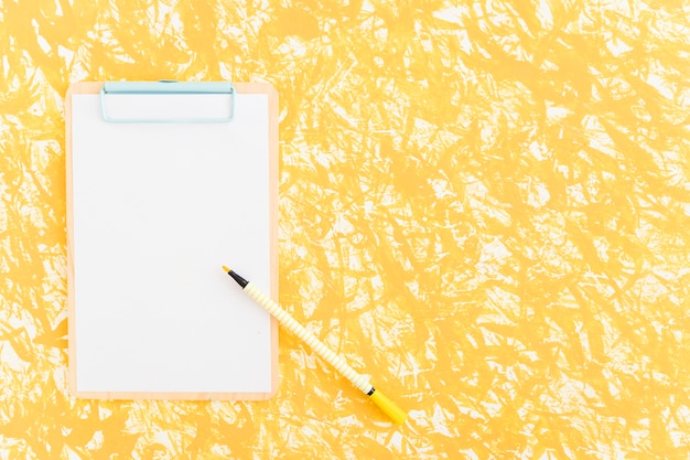 Felt tip pen on clipboard over the yellow textured backdrop Free Photo