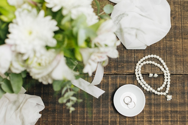 Female accessories; wedding rings ; scarf and flower bouquet on table Free Photo