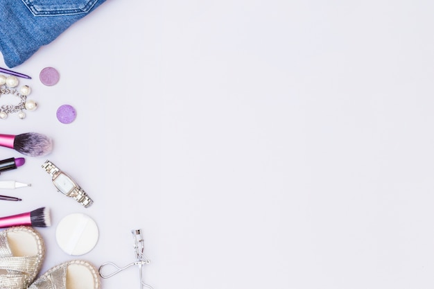 Female accessory with cosmetics products on white backdrop Free Photo