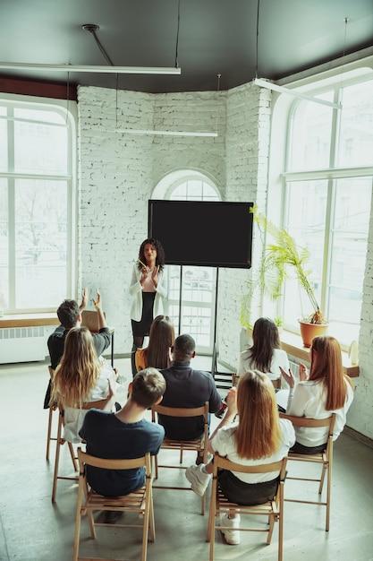 Female african-american speaker giving presentation in hall at university workshop Free Photo