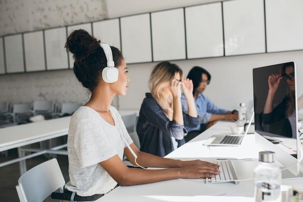 Женский африканский сотрудник call-центра с помощью компьютера и разговаривает с коллегами. внутренний портрет менеджеров международной компании, работающих в большом офисе. Бесплатные Фотографии