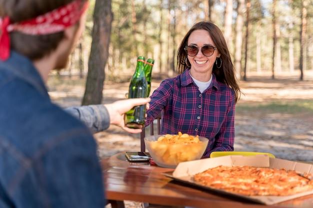 Тост с пивом над пиццей друзей женского и мужского пола Бесплатные Фотографии