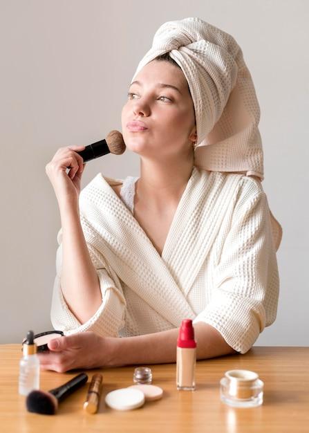 Female applying blush Free Photo