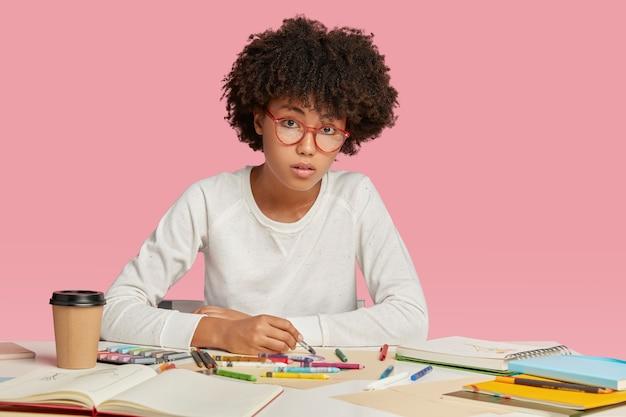 여성 건축가는 아프로 헤어 스타일을 가지고 있고, 프로젝트를 디자인하고, 노트북에 그림을 그리며, 진지하게 보이고, 안경을 쓴다. 무료 사진