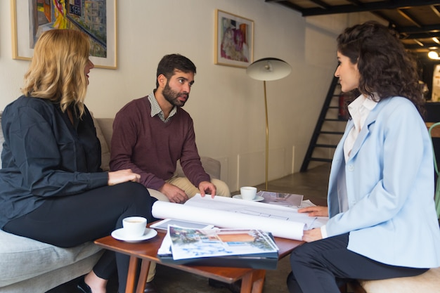 Female architect presenting floor plan and discussing blueprint Free Photo