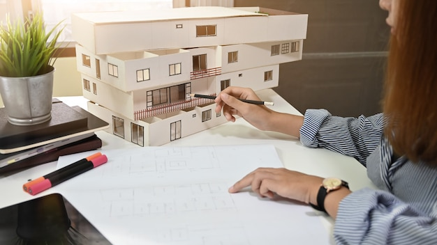 Female architect working with model house and blueprint in home office. Premium Photo