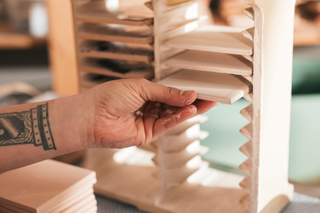 Female artisan arranging the painted white ceramic tiles in the small rack Free Photo