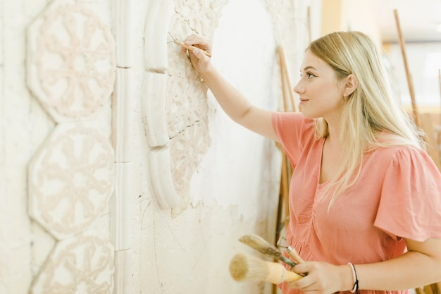 An female artist carving on wall with tool Free Photo