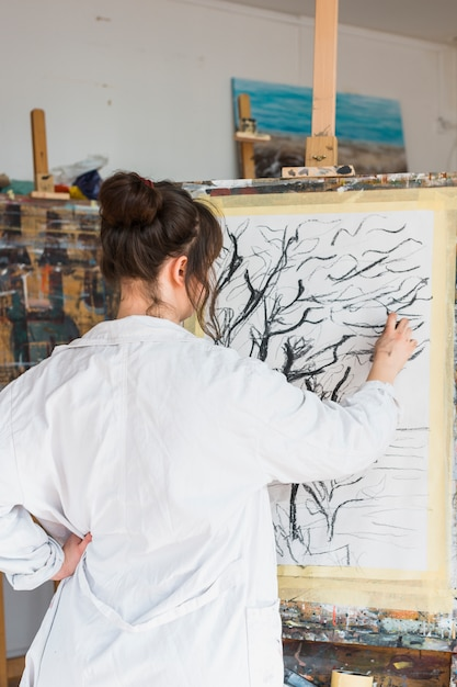 Female artist drawing creatively on canvas with charcoal Free Photo