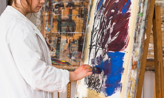 Female artist painting with brush on canvas at workshop Free Photo