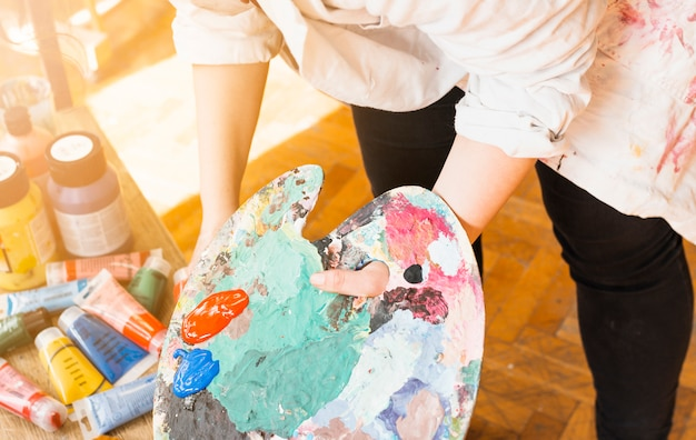 Female artist's hand holding messy paint palette at workshop Free Photo