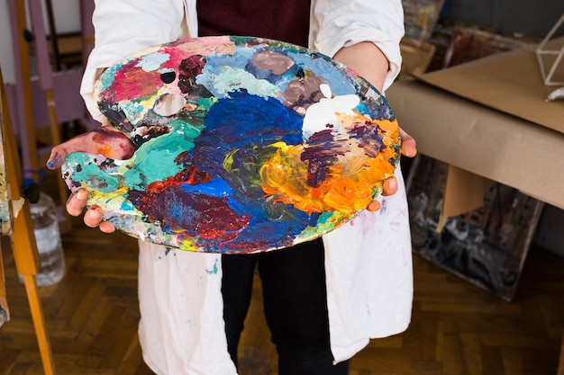Female artist's hand showing messy color palette Free Photo