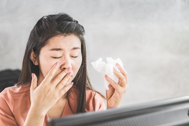 Female asian having flu sneezing at workplace Premium Photo