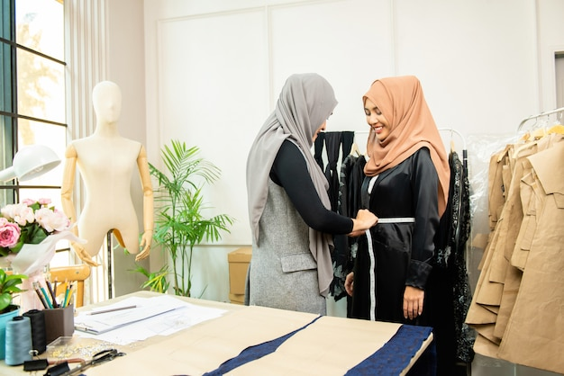 Female asian muslim designer measuring waist of customer Premium Photo