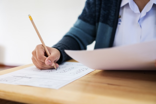 Female asian students hands taking exams, holding pencil writing on optical form in examination room Premium Photo