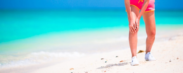 Female athlete suffering from pain in leg while exercising on white beach Premium Photo