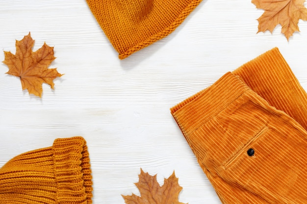 Female autumn clothing, warm knitted scarf and cap orange colored and trousers from corduroy. Premium Photo